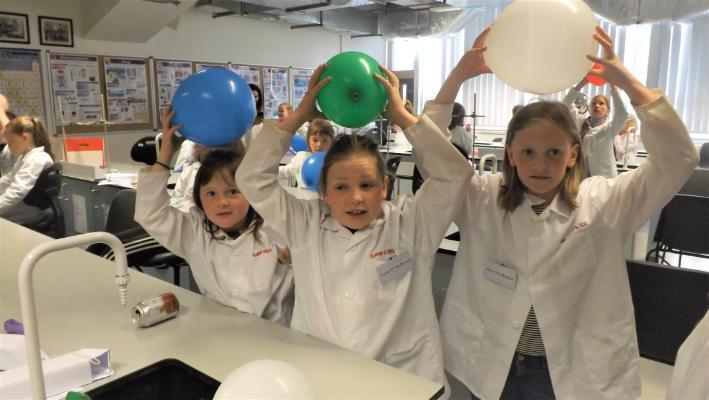 Three girls using balloons to create static electricity which pulls the hair up