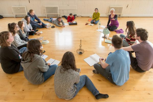 Theatre students in a circle learning