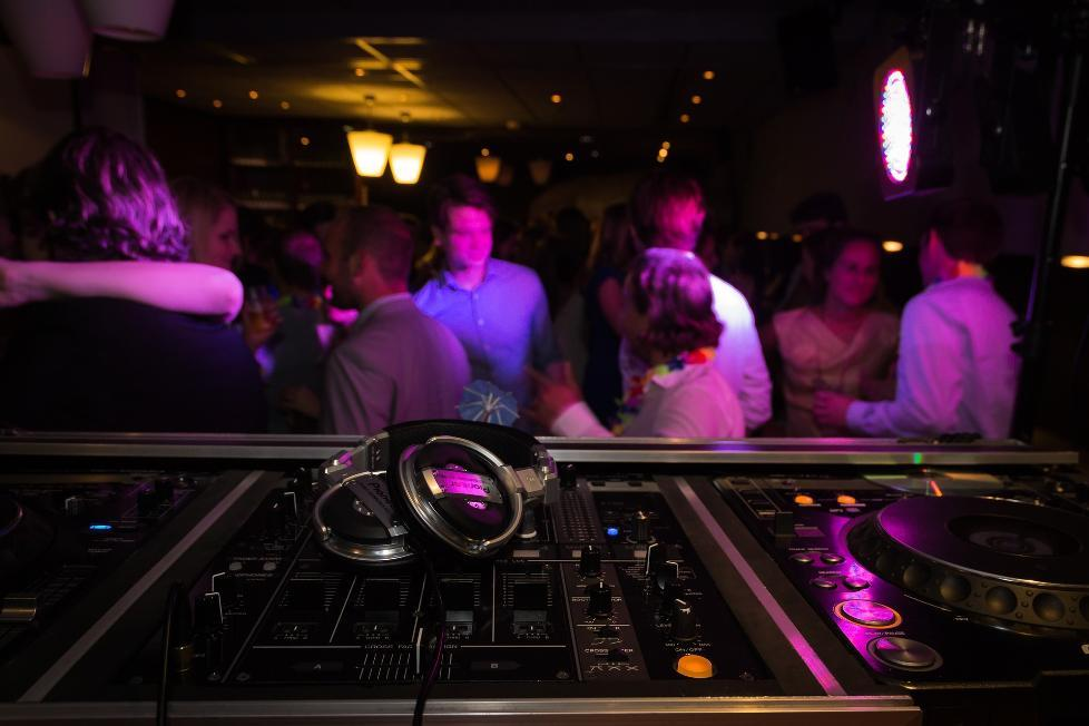 foreground of DJ's mixing desk with people dancing in the background out of focus