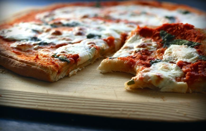 Close up shot of pizza on a wooden board